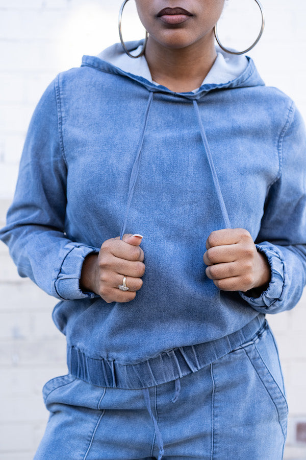 Model pulling draw strings on Relaxed Denim Tracksuit