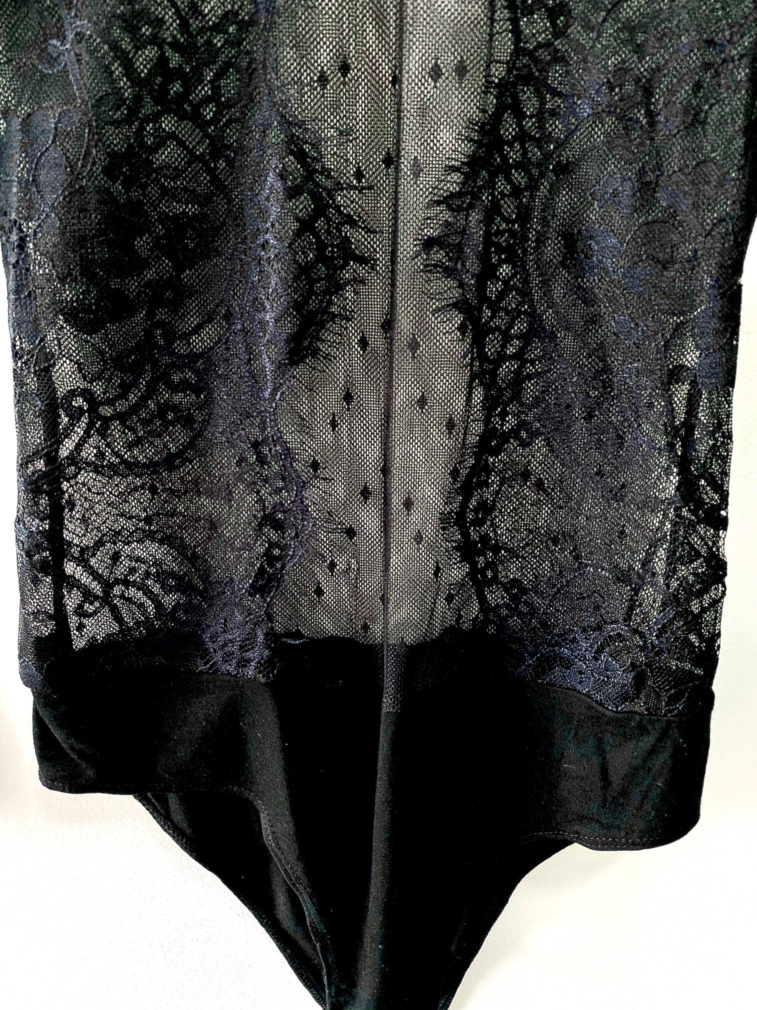snap closure at crotch of black lace body suit