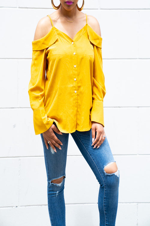 Model wearing yellow button down open shoulder blouse and denim jeans