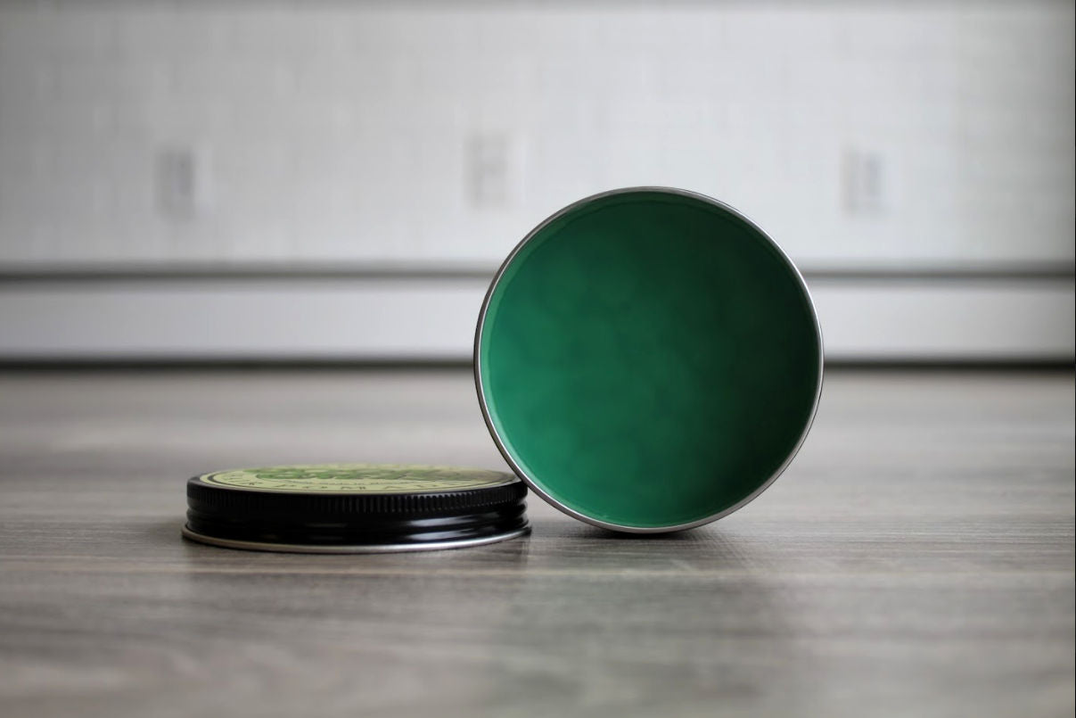 goon grease open can with texture and signature green pomade inside.