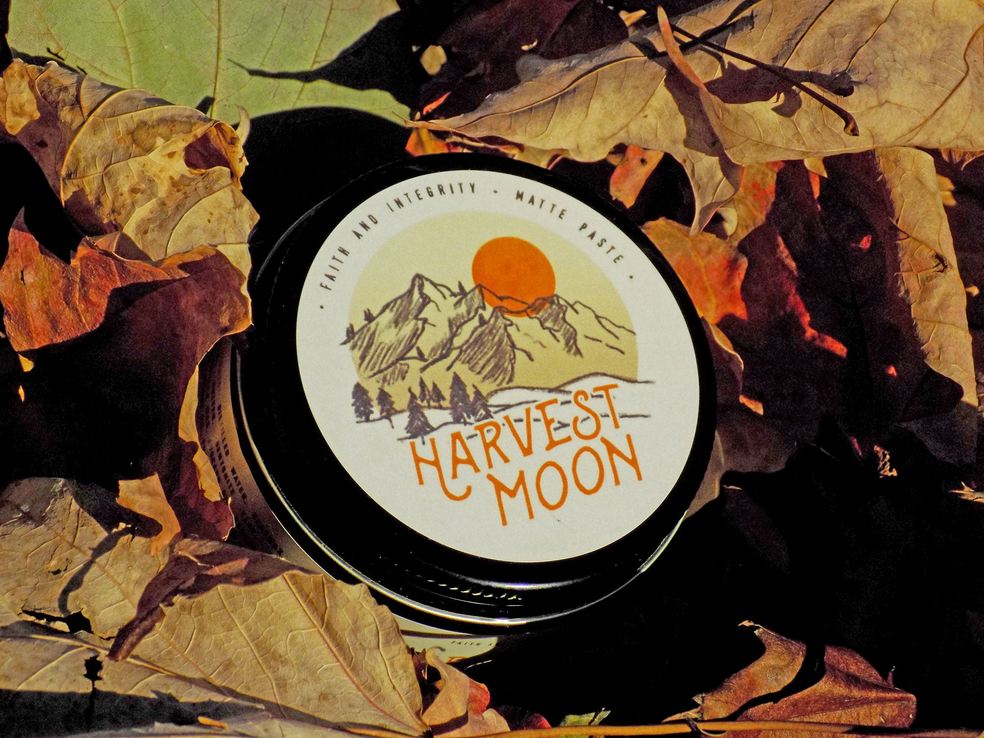 Faith and Integrity Harvest Moon matte paste sitting in a bed of fall leaves. Used for matte and texturized hairstyles.