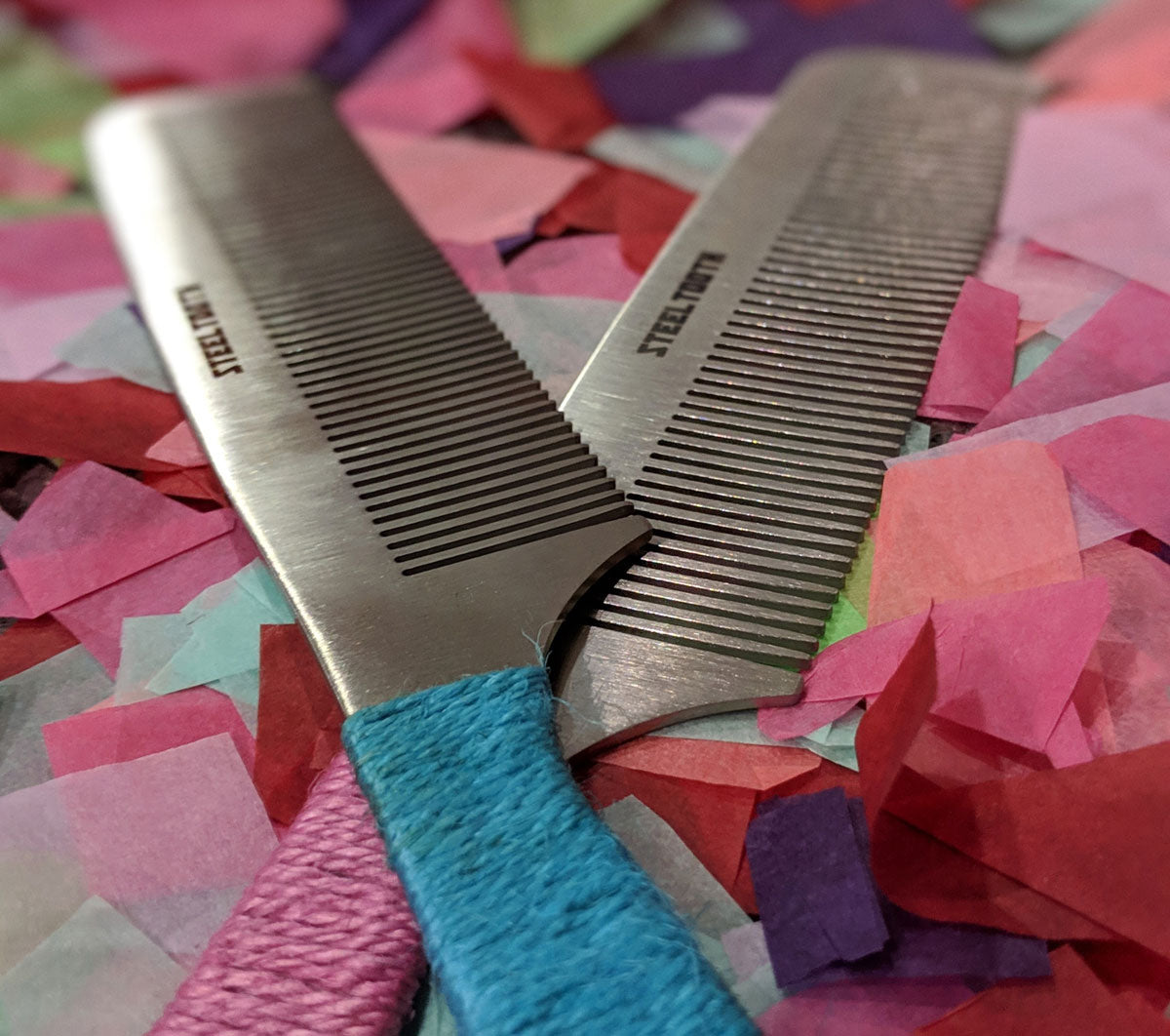 Two combs one with pink and the other a blue handle.
