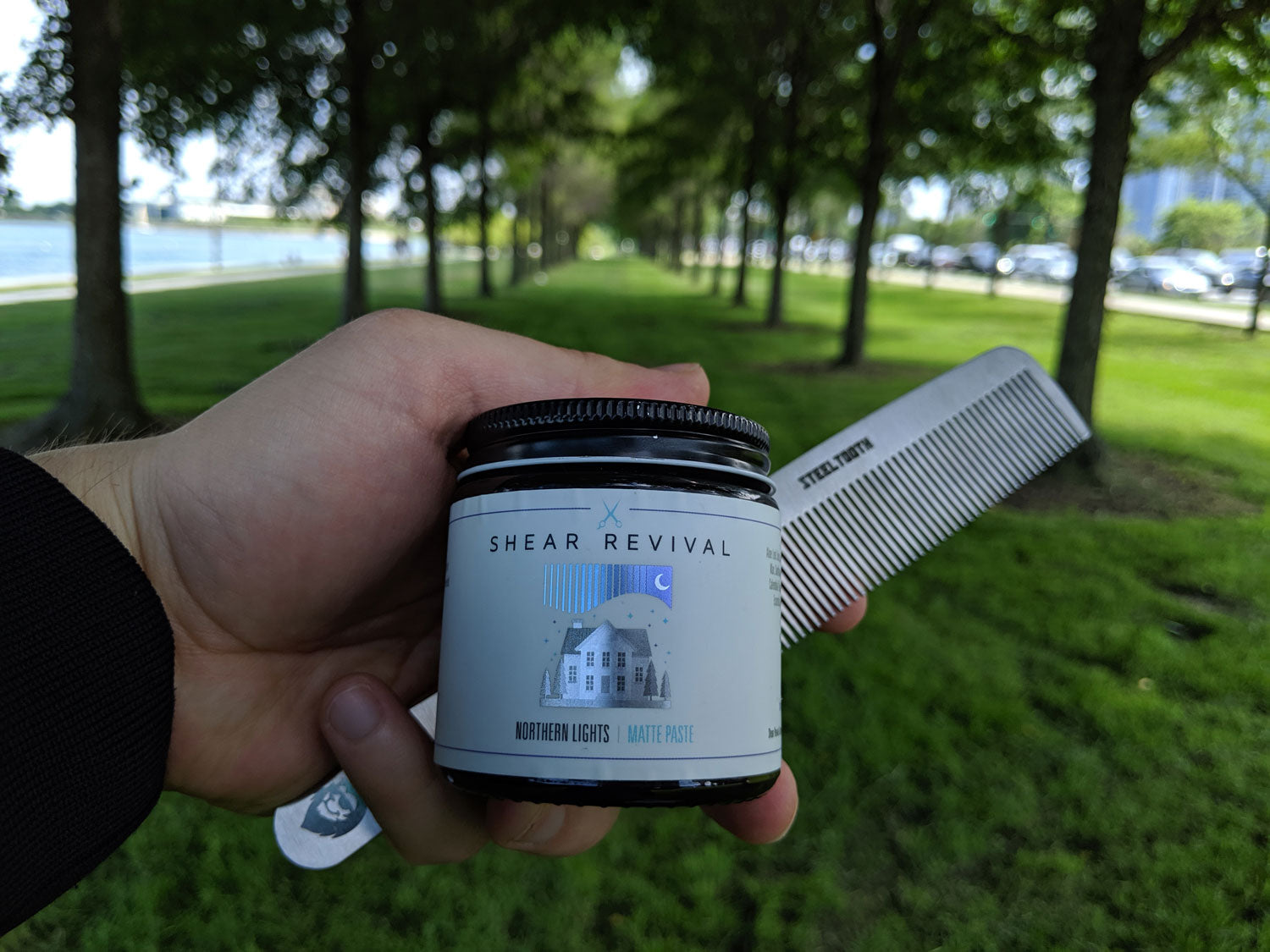 A man holding shear revival matte paste and a steeltooth comb near the lakefront in chicago.