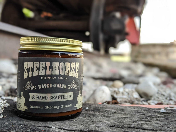 Steelhorse supply co. pomade on a railroad track.