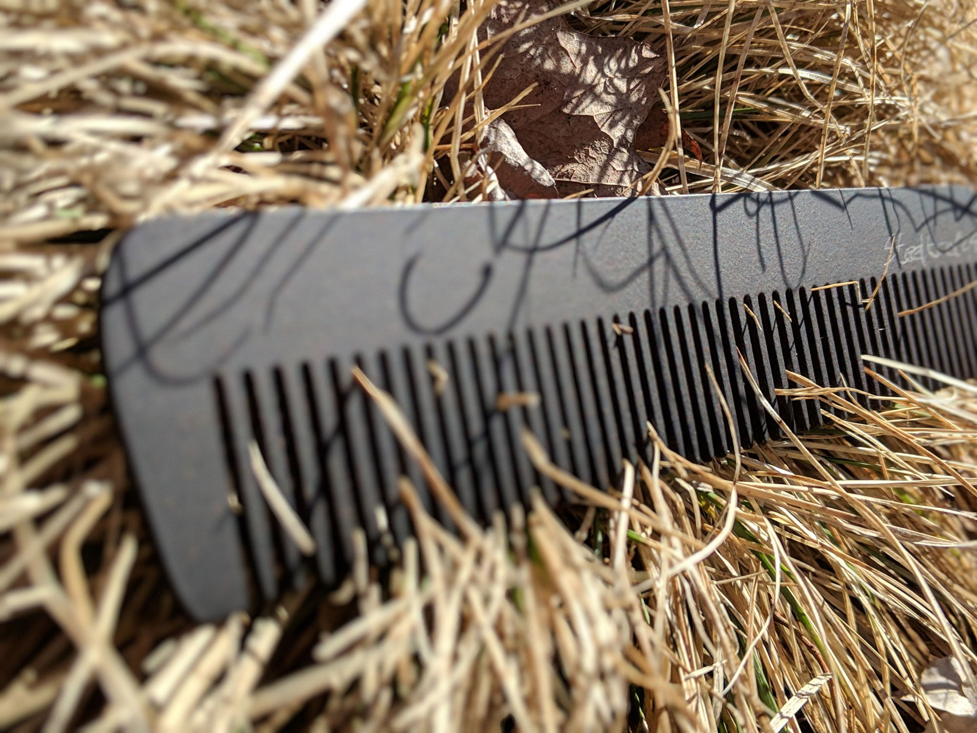A steeltooth new standard comb with a deep red/brown finish on it in some dead grass.