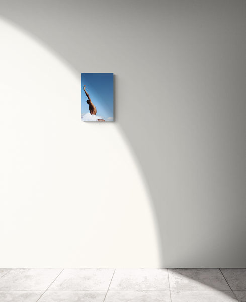 Black male dancing in the nature. His hand is oriented up onto the blue sky. We see him from behind. his armpit is glowing into the sunlight. Art print on a white wall.