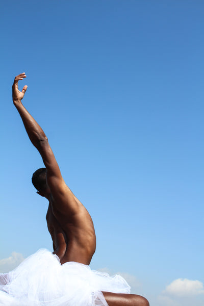Black male dancing in the nature. His hand is oriented up onto the blue sky. We see him from behind. his armpit is glowing into the sunlight.