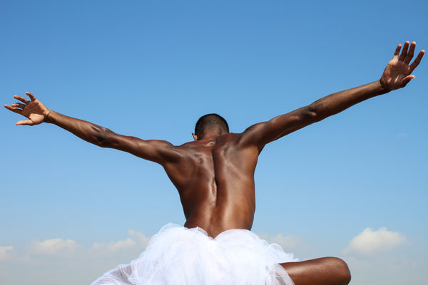 With open arms, we see a black male spreading his hands like wings into the blue sky.