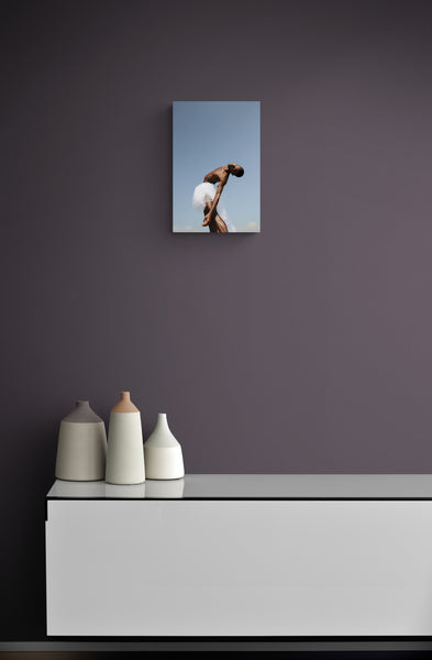 Black male dancer in a meditative movement mood. his skin is glowing into the sun. He is wearing a white skirt on a perfect blue natural sky background. Art print on the wall.