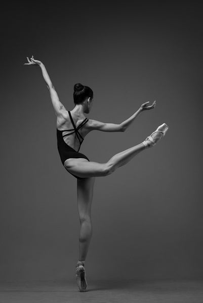 Ballerina, en pointe, dancing, attitude. Photo print studio, back shoot, colors black and white.