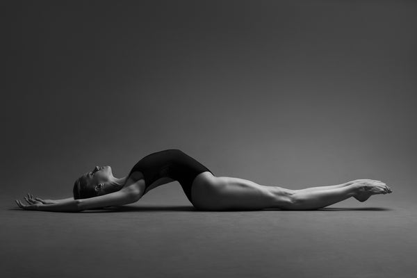 Ballerina, stretching on the floor, body arch, breathing. Photo print studio, colors black and white