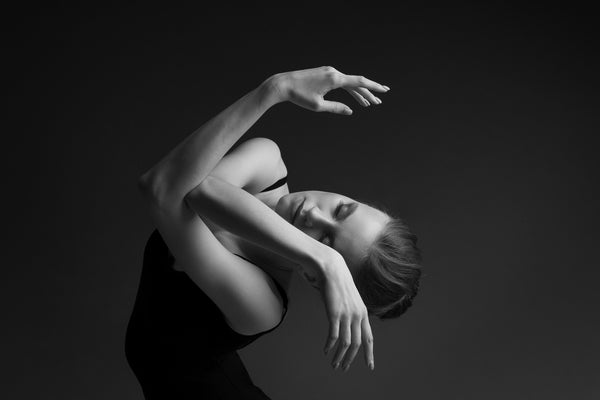 Dancer, female, portrait, close-up. Intertwined hands, in front of the face, eyes closed. head is on the side. she is dancing.