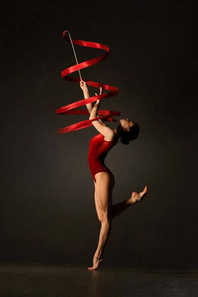 Female gymnast, red bodysuit, practicing, ribbon, red.