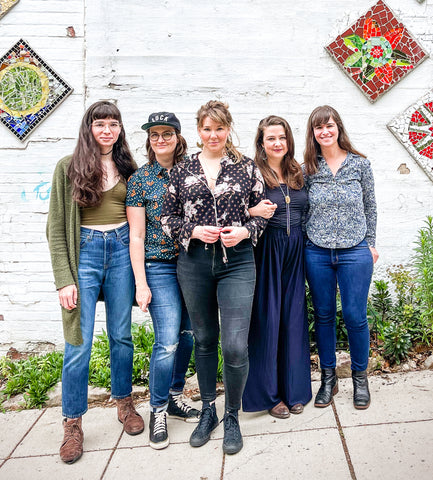 Image of band members of Della Mae, from left to right: Maddie Witler (mandolin), Kimber Ludiker (fiddle and vocals), Celia Woodsmith (guitar and vocals), Vickie Vaughn (bass and vocals), and Avril Smith (guitar).