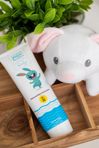 Natural baby sunscreen from California Pure Naturals shown with a white stuffed bunny next to it.