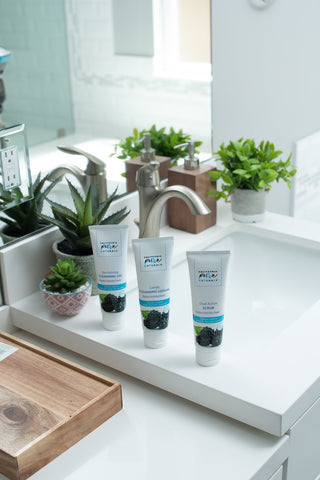 Organic facial washes and organic facial lotion from California Pure Naturals, showing California Pure Naturals' products Revitalizing Cleansing Gel, Gentle Cleansing Lotion, and Dual Action Scrub from left to right next to a sink.