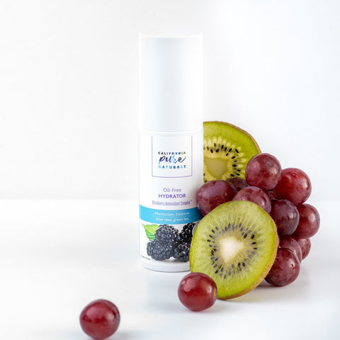A bottle of natural oil-free moisturizer that's organic and 100% vegan from California Pure Naturals, with grapes and kiwis around it