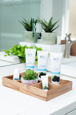 Organic and vegan facial skin care products from California Pure Naturals in a tray on a bathroom counter to be used in a normal skin care routine.