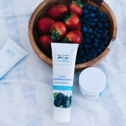 Cleansing Lotion and Nourishing Cream products by California Pure Naturals with strawberries and blueberries in a bowl behind products, highlighting the ingredients from which products are made.