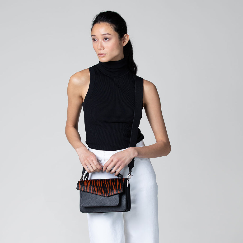 botkier cobble hill structured asymetric flap crossbody in black with tiger haircalf flap