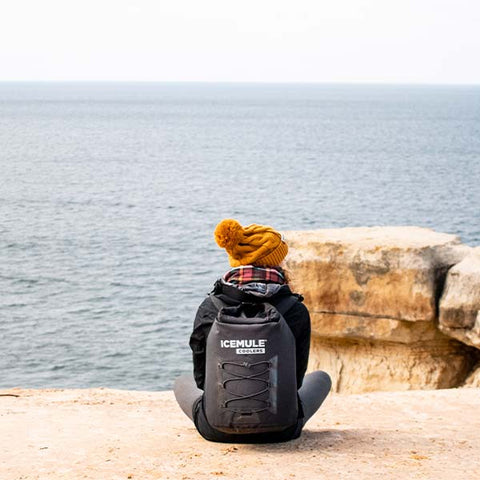 A hiker wears her IceMule cooler overlooking the ocean from a beachside cliff.
