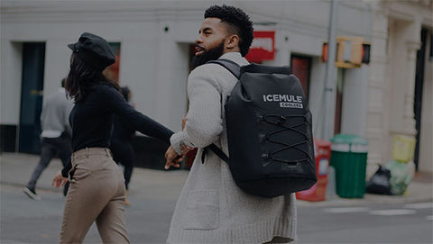 A group of friends walks through the city with their IceMule cooler in tow.