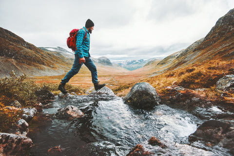 A hiker make his way across a small stream in the mountains of Scandinavia.