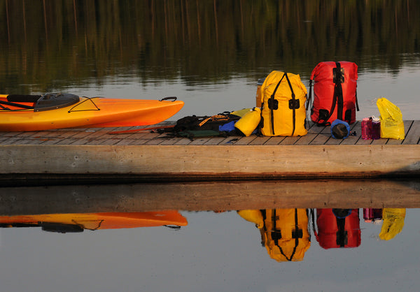 Packed up dry bags and backpacks on the dock beside a kayak on a river.