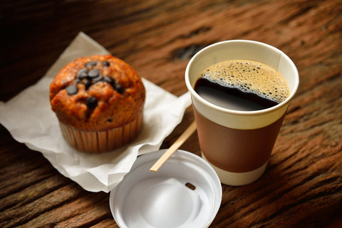 Coffee and a muffin on a wooden table background.