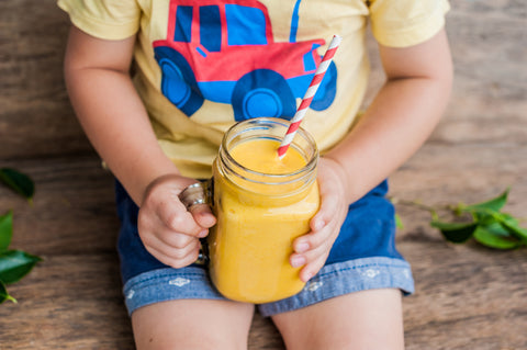 A kid drinks fresh orange juice out of a mason jar.