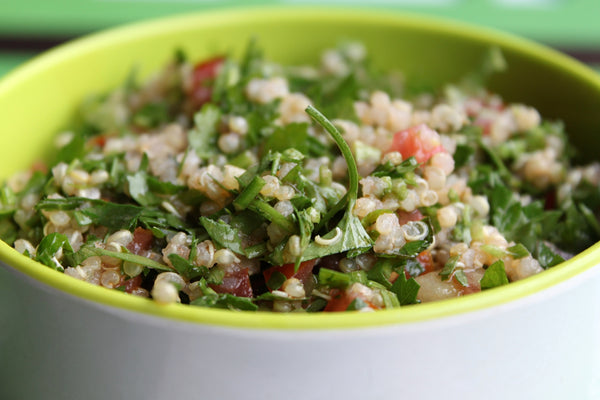 Quinoa tabouleh in a green bowl