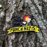 A yellow Punch Nazis enamel lapel pin with a moving arm that actually punches
