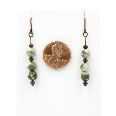 Handmade In Conifer Jewelry - Copper Rainforest Jasper Earrings next to coin for size