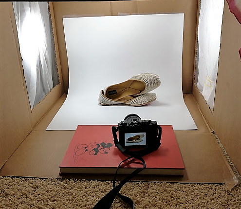 A DIY lightbox made from cardboard box with light shining from both sides, a white poster board as background. A white beaded mochiis flats is being pictured with a camera resting on a red book with mickey mouse on the cover.