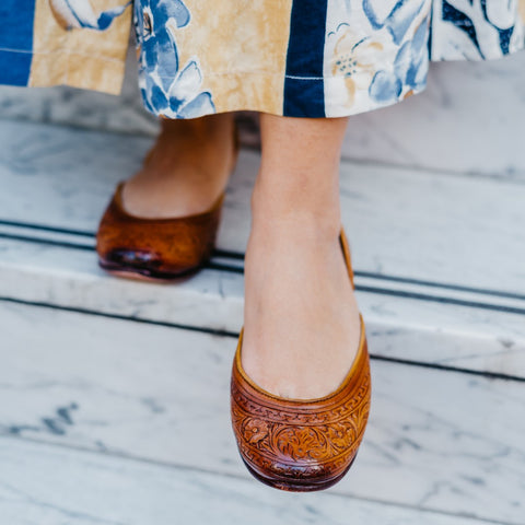 hand tooled brown leather flat shoes on foot