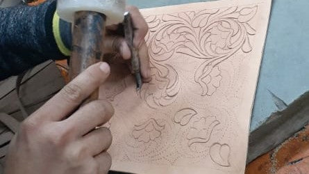 Artisan hand tooling a leather piece