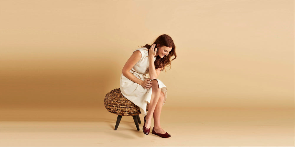 Woman sitting on a wicker stool in a white dress wearing maroon hand-carved handmade leather flats shoes