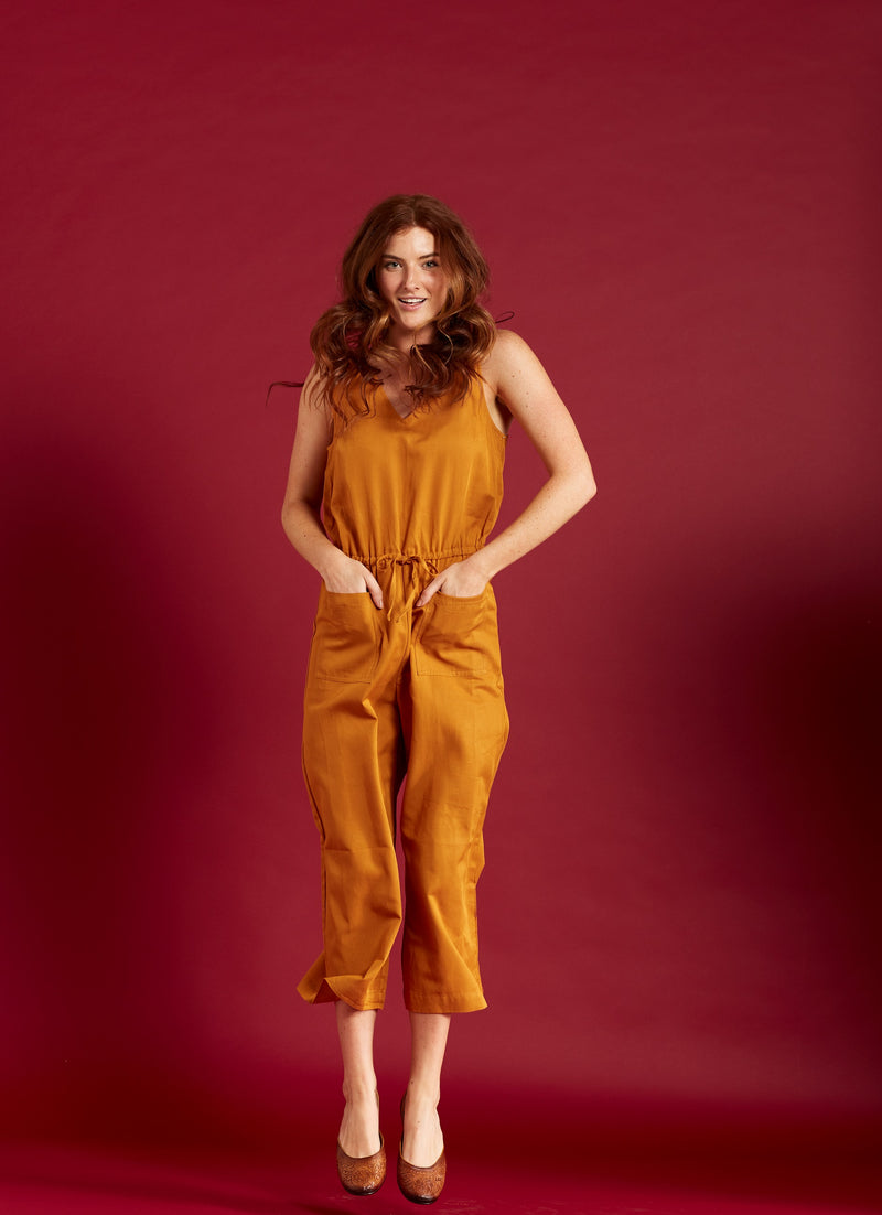 Woman in a rust colored jumpsuit wearing hand-carved handmade leather flat shoes