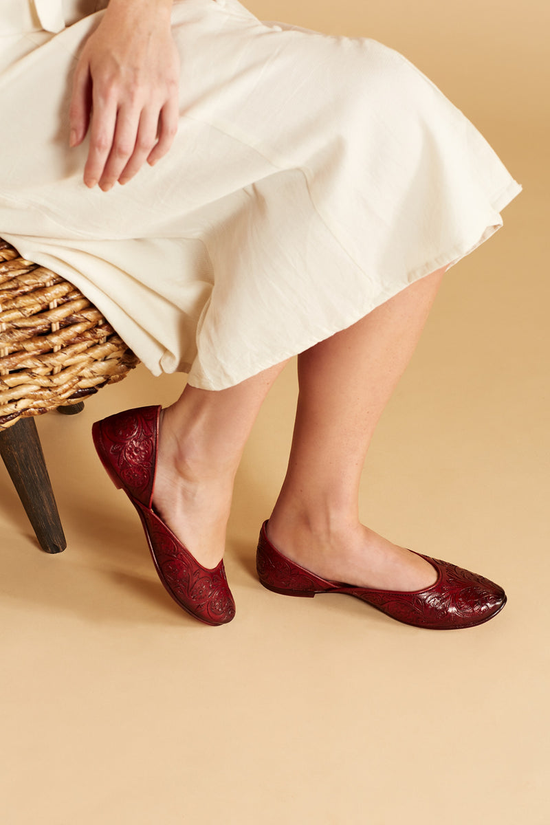 Woman in white dress wearing a maroon handmade leather flat shoes with hand-carved floral design