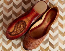 Hand-carved brown flat shoes on a textured surface with a paisley design on the sole that says Mochiis Footwear