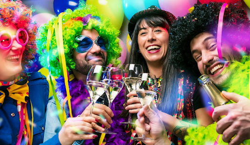 Youngsters wearing Mardi gras costumes with wigs in a party