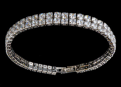This Silver Color 2 Row Diamond Bracelet weighs approximately 31 grams and showcases zirconia diamonds. Featuring a 2 row design and a luxurious rhodium plating for extra shine, this silver diamond bracelet is an affordable alternative to gold jewelry. The listing is for the bracelet in 7.5