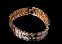Add this beautiful woven design is plated of quality 14 karat yellow gold bracelet. The bracelet is seven and 1/2 inches in length, measures just over 1/2 of an inch wide, and is secured by a lobster clasp.