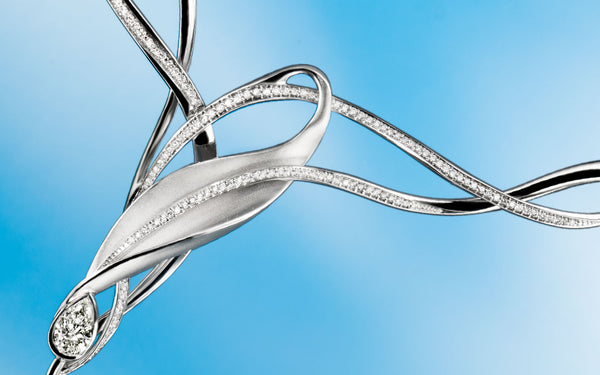 Artistic, complex shape designed jewellery parts, highlighted by line of sparkling briliant cut diamonds