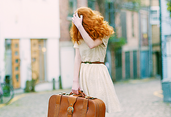 woman holding suitcase covering face