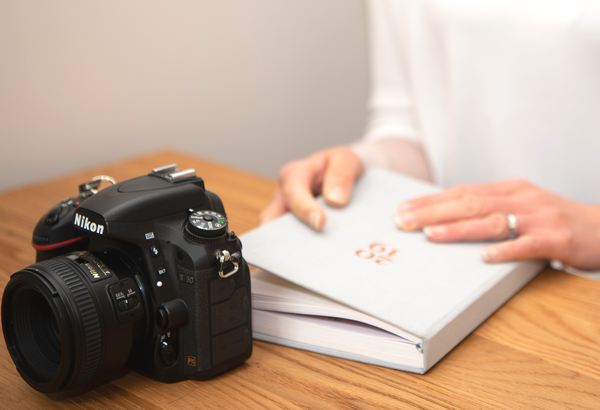 Picture by Victoria Murray of woman holding the Ponderlily planner with a camera.
