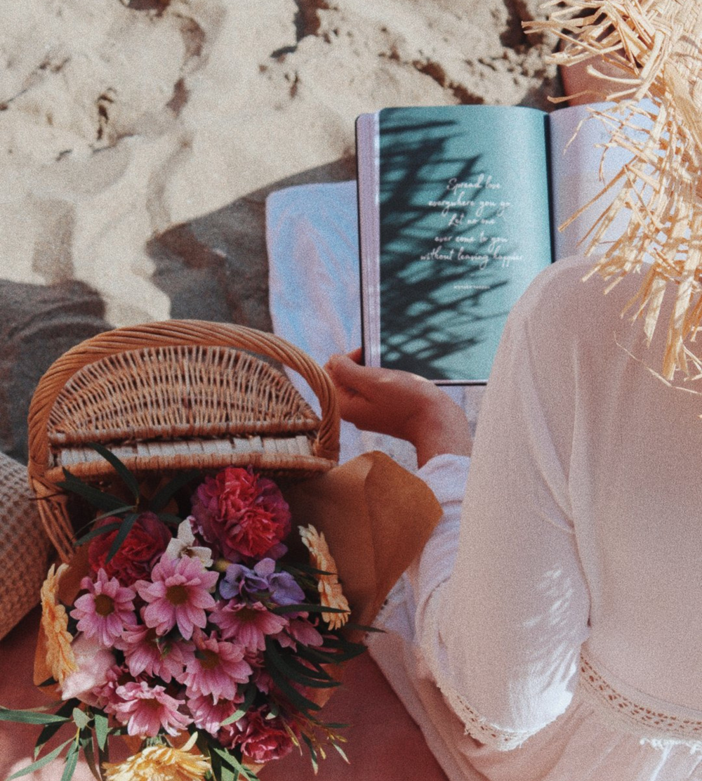 Woman reading a Ponderlily planner by the beach