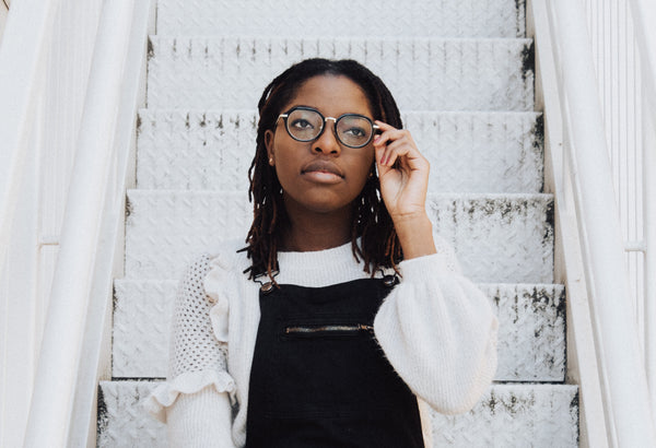 Black woman wearing glasses sitting on stairs