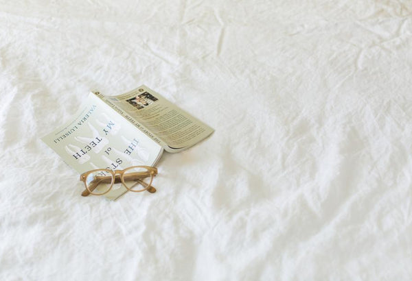 book on a bed and reading glasses