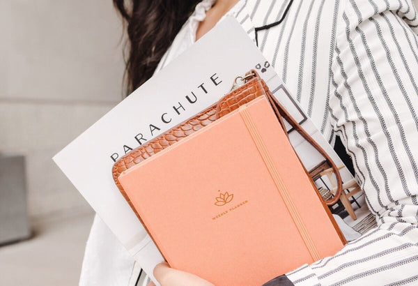 A woman holding undated weekly 2021 Ponderlily Planner in coral